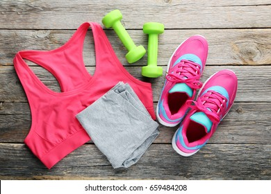 Pink sport shoes with sportswear and dumbbells on grey wooden table
