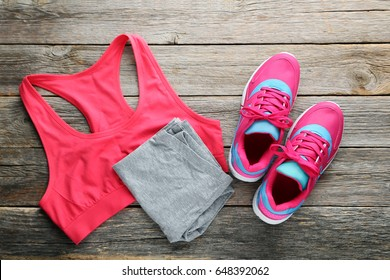 Pink sport shoes with sportswear on grey wooden table
