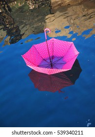 Pink spotted upturned umbrella floating on water surface