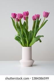 Pink spring tulip flowers in ceramic vase