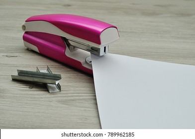 A pink stapler with papers and a pile of staplers on a table