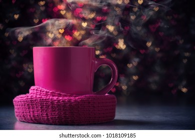 Pink steaming cup in scarf over heart shaped defocused lights.