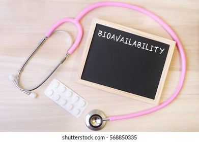 A pink stethoscope, a blister of tablets and a blackboard with word BIOAVAILABILITY on top of wooden background. Medical, health and education concepts.