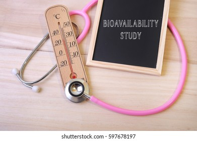 Pink stethoscope and a thermometer with a notice board with word BIOAVAILABILITY STUDY on top of wooden table. Medical and education concept.