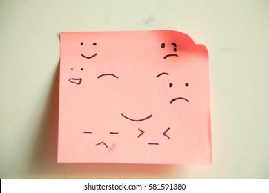 Pink sticky paper note emotion face.