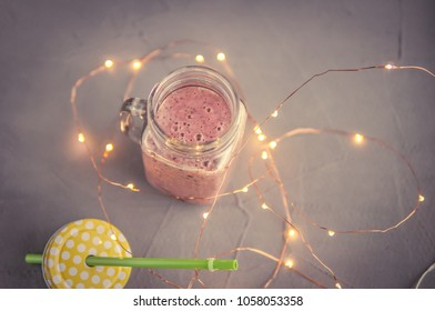 Pink strawberry cocktail smoothie over gray background, toned image