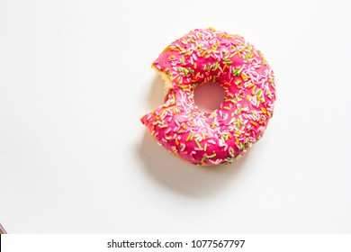Pink strawberry donut bitten from one side at white background