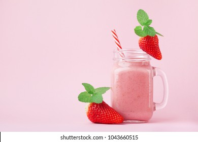 Pink strawberry smoothie or milkshake in mason jar decorated mint on pastel background. Healthy food for breakfast and snack.