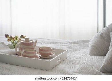 Pink striped teaset on breakfast tray in bedroom