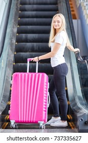 Pink suitcase with a young girl on the escalator