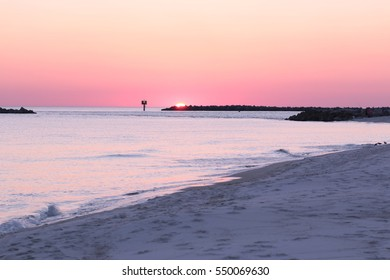 pink sun going down behind horizon on the gulf coast at orange beach pass