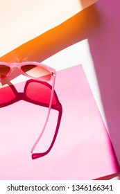 Pink sunglasses on pink and yellow background with shadows. Pop art conception.