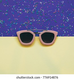 pink sunglasses on yellow and ultra violet magic colored background. minimalism and creative concept