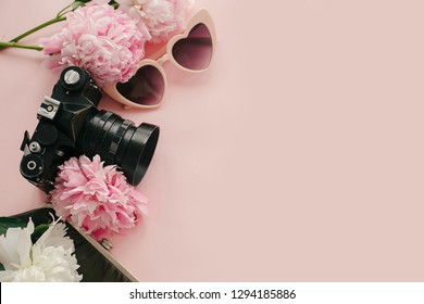 Pink sunglasses, photo camera and vintage purse with pink and white peonies on pastel pink paper. Flat lay with copy space. Hello spring. Summer vacation. International Womens Day.