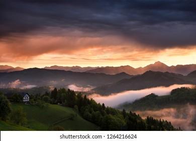 Pink sunrise and blue clouds in the mountains of Kamnik Savinja Alps with Storzic peak on right and fog over Skofjelosko Hills near Ljubljana Slovenia