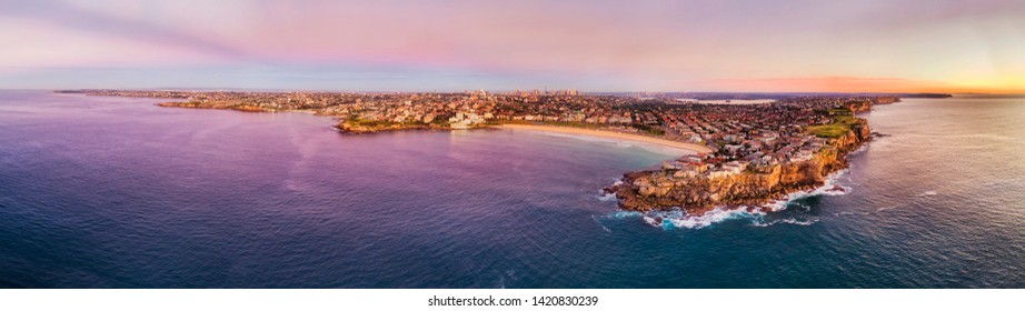 Pink sunrise from Pacific ocean over Sydney city coast around Bondi beach between sandstone cliff headlands of eastern suburbs - iconic beach of Australia.
