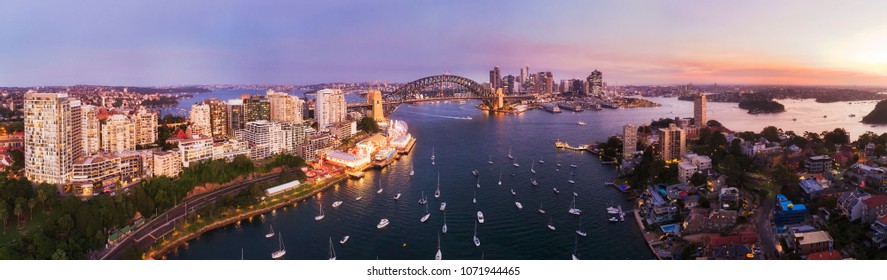 Pink sunset over Sydney city CBD landmarks around Sydney harbour connected by the Sydney harbour bridge in elevated aerial panorama from Lavender bay and North Sydney shores.