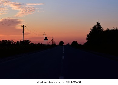 pink sunset with the road and wires