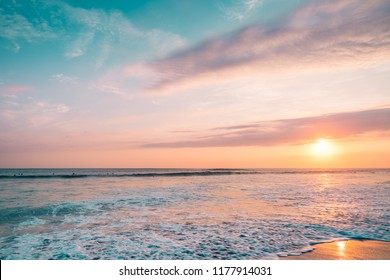 Pink Sunset Sea with Surfers.  Colorful Landscape of Paradise Tropical Island Beach, Sunrise Surfing Shot. Blue & Pink Barrel Wave in Ocean. Clear Surfers Wave and Sun Light. Ocean Water Background.