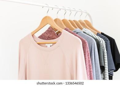 Pink Sweatshirt Hanging on Rack with Other Shirts