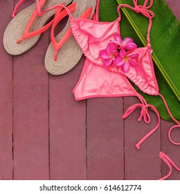 Pink Swimsuit Slippers Frangipany Tropical Flowers on Palm Leaf Wooden Background Near Swimming Pool Tropical Resort Travel