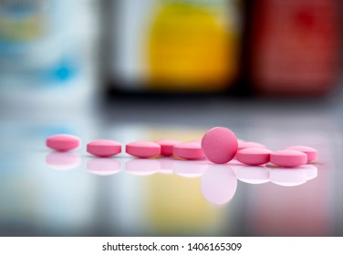 Pink tablets pills on blurred background of drug bottle in drugstore or pharmacy department in hospital. Pharmaceutical industry. Pharmaceutics concept. Medicine for treatment illness. Healthcare.