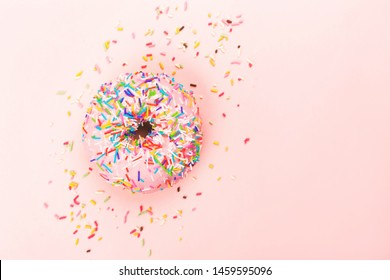A pink tasty doughnut with colorful sprinkles on pink background. Flat lay, top view.