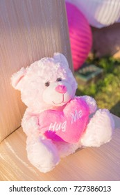 Pink teddy bear holding a heart that reads hug me in letters on heart