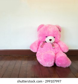 Pink teddy bear sitting against a white wooden wall.