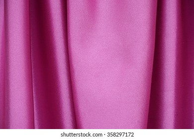 Pink textile with folds for background. Straight elegant curves of luxury shiny silk, satin or velvet fabric.