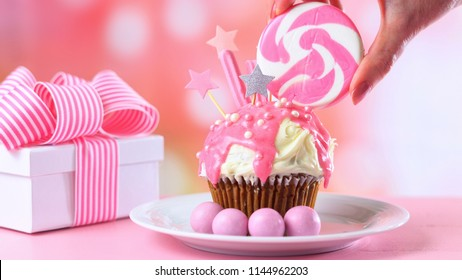 Pink theme colorful novelty cupcake decorated with candy and large heart shaped lollipop for children's or teen's birthday, Valentine's or Mother's Day celebrations.
