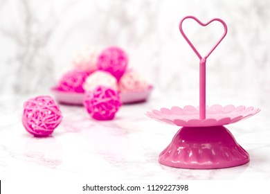 Pink tier serving tray on white marble background