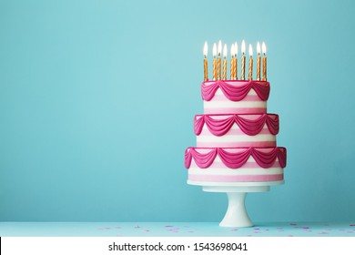Pink tiered birthday cake with birthday candles - Shutterstock ID 1543698041