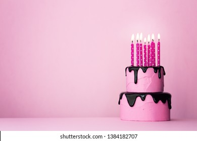 Pink tiered birthday cake with drip icing and lots of candles