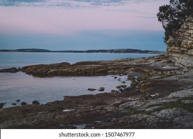 pink toned twilight over deserted beach with rugged rocks in Tasmania, Australia