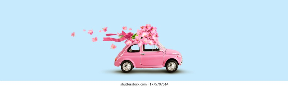 Pink toy car with bouquet of flowers on a roof with ribbon and bow on blue background. Flowers delivery.
