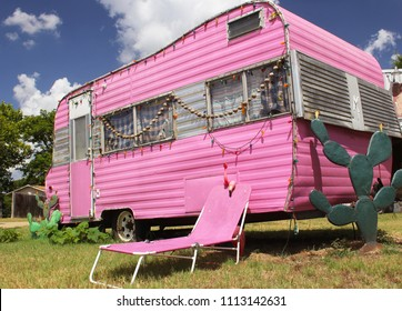 Pink Travel Trailer with Chair and cactus with blue sky and clouds