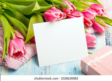 Pink tulip bouquet, gift box and balnk paper on blue wooden background, copy space.