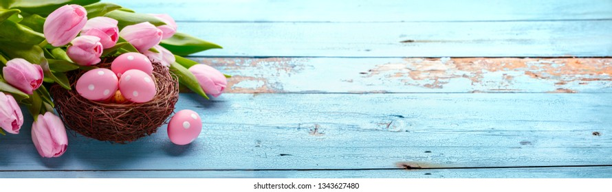 Pink tulip flower and eggs on wooden background