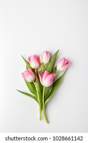 Pink tulip flowers bouquet on white background. Flat lay, top view.