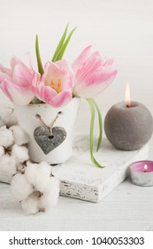 Pink tulip flowers, lit candles on white wooden background