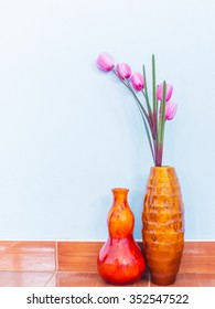 Pink tulip in wooden painted brown vase over blue wall background