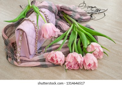 Pink tulips with bag and scarf on wooden background