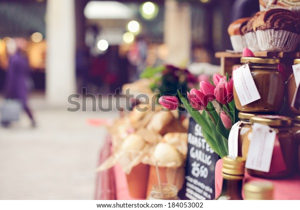 Pink tulips, baked goods, homemade preserves and jams on a farmer's market stand