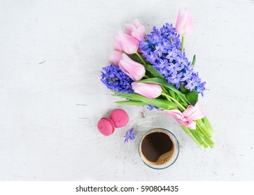 Pink tulips and blue hyacinths flowers with cup of coffee on white wooden table with copy space