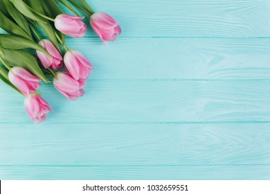 Pink tulips bouquet on blue wooden background, copy space and flat lay.