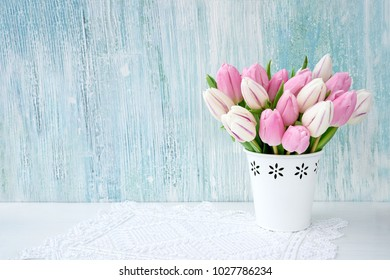 Pink tulips bouquet in white vase on blue background. Holiday background, copy space. Valentine Day, Mothers day, birthday concept.