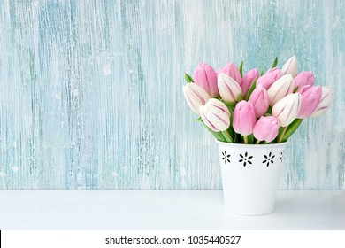 Pink tulips bouquet in white vase on light blue background. Holiday background, copy space. Valentine Day, Mothers day, birthday concept.