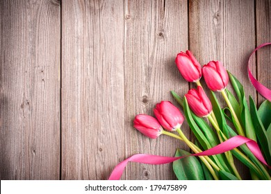 Pink tulips with a bow on wooden background with copy space for text