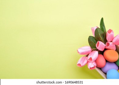 Pink tulips in box and Egg Easter on paper yellow background copy space for text